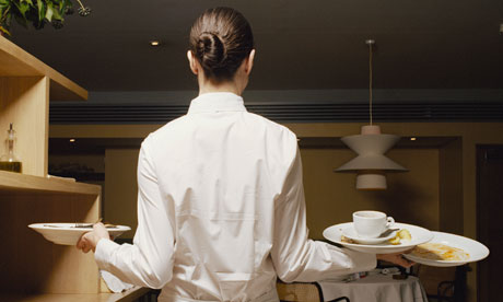 Waitress carrying dirty plates in restaurant, rear view
